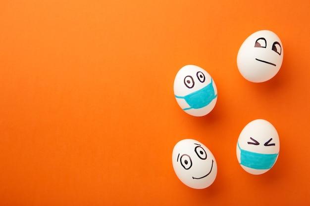 Ovos de páscoa brancos em máscara médica protetora e dois ovos sem máscara em fundo laranja.
