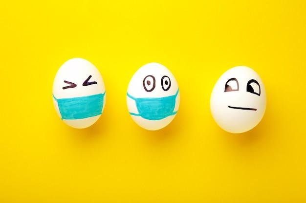 Ovos de páscoa brancos em máscara médica protetora e um ovo sem máscara em fundo amarelo.