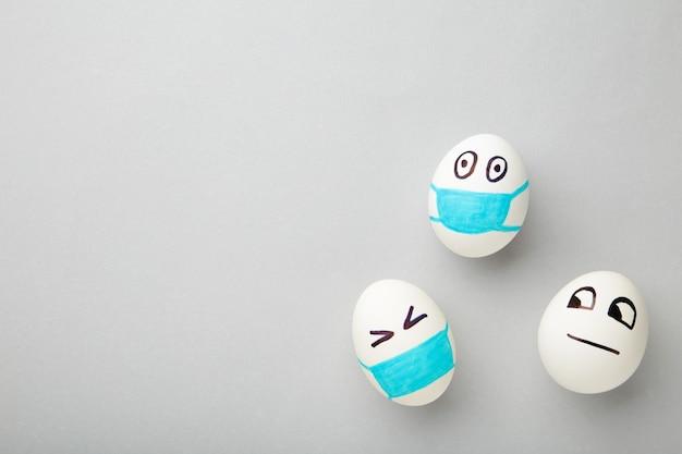 Ovos de páscoa brancos em máscara médica protetora e um ovo sem máscara em fundo cinza.