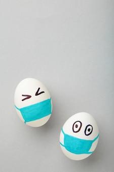 Ovos de páscoa brancos em máscara médica protetora em fundo cinza