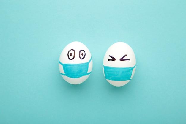 Ovos de páscoa brancos em máscara médica protetora sobre fundo azul. e