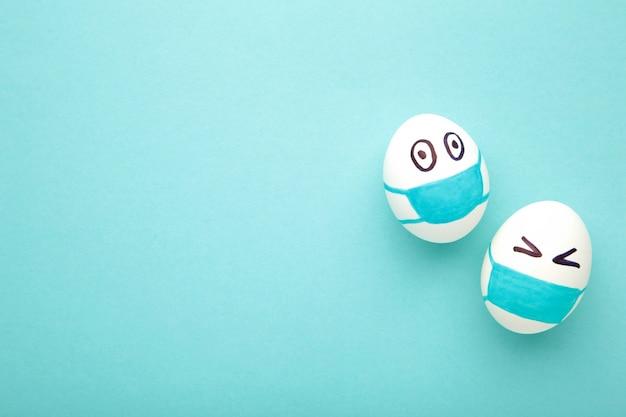 Ovos de páscoa brancos em máscara médica protetora sobre fundo azul.