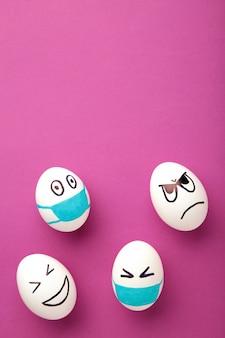 Ovos de páscoa brancos na máscara médica protetora e dois ovos sem máscara no fundo rosa.