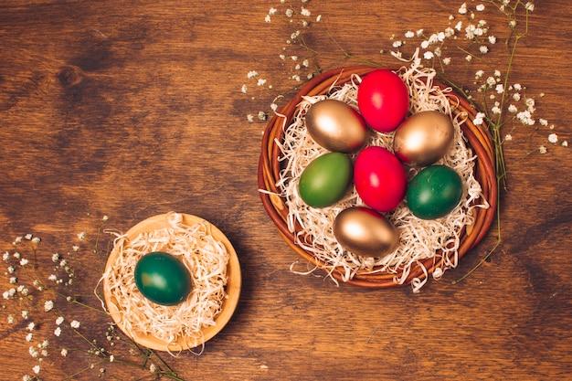 Ovos de páscoa brilhante em pratos com ouropel perto de plantas