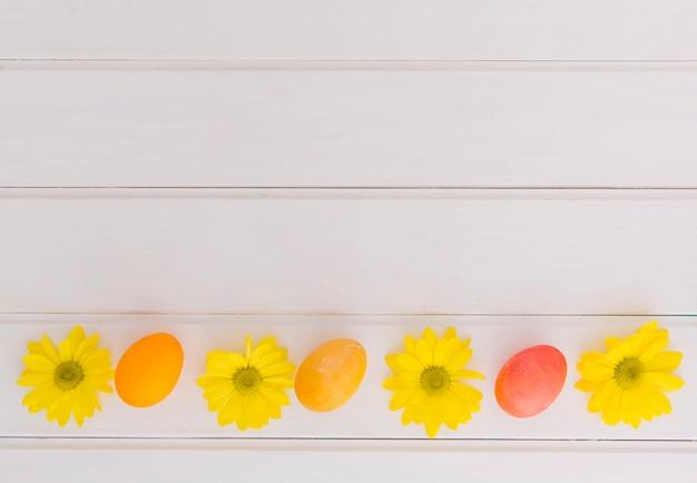 Ovos de páscoa brilhantes e flores amarelas na mesa