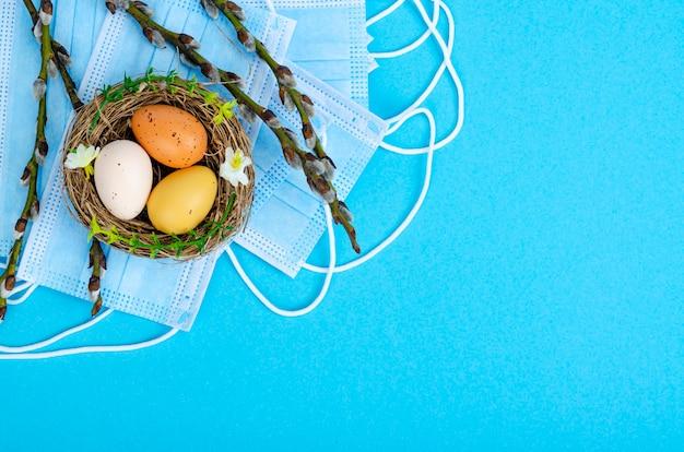 Ovos de páscoa brilhantes máscaras médicas ramos de salgueiro. parar o vírus covid19