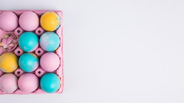 Ovos de páscoa brilhantes no recipiente rosa