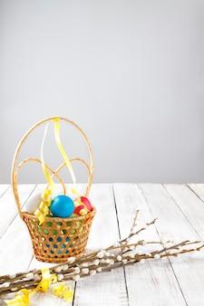 Ovos de páscoa brilhantes pintados em uma cesta de vime e galhos de salgueiro com fita amarela em uma mesa de madeira clara. copie o espaço