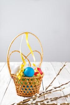 Ovos de páscoa brilhantes pintados em uma cesta de vime e ramos de salgueiro em uma mesa de madeira clara. copie o espaço