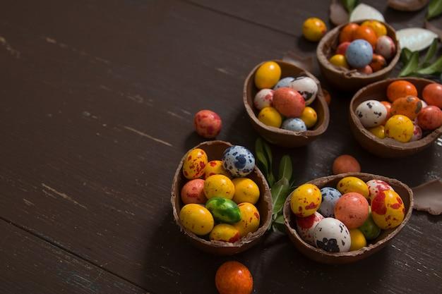 Ovos de páscoa caçam fundo com ovos de chocolate em fundo de madeira