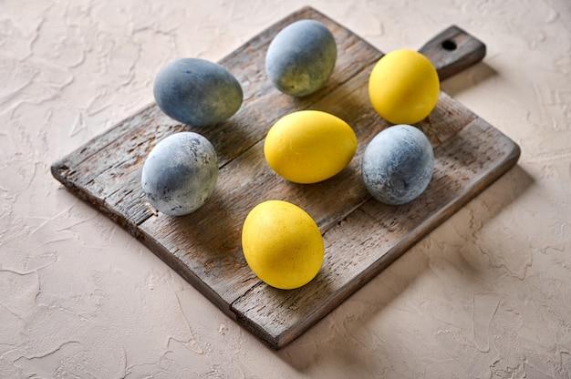 Ovos de páscoa caseiros coloridos de mármore amarelo e cinza na tábua de madeira envelhecida fecham seletivamente