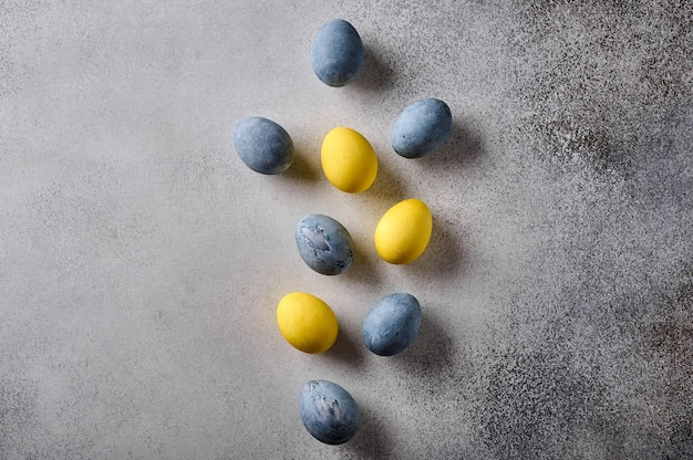 Ovos de páscoa caseiros coloridos em mármore amarelo e cinza na mesa de madeira, vista de cima, cópia espaço