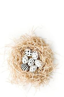 Ovos de páscoa chiques no ninho na superfície branca