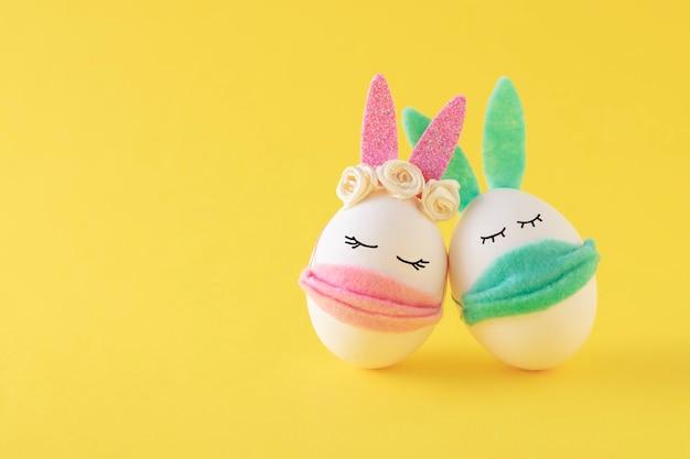 Ovos de páscoa-coelho usando máscaras protetoras em uma parede amarela. concept covid-19, fique em casa.
