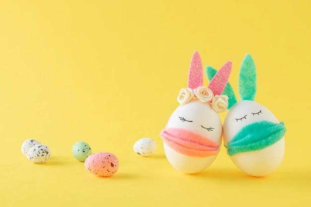 Ovos de páscoa-coelho usando máscaras protetoras em uma parede amarela. decoração de férias da páscoa. concept covid-19, fique em casa.