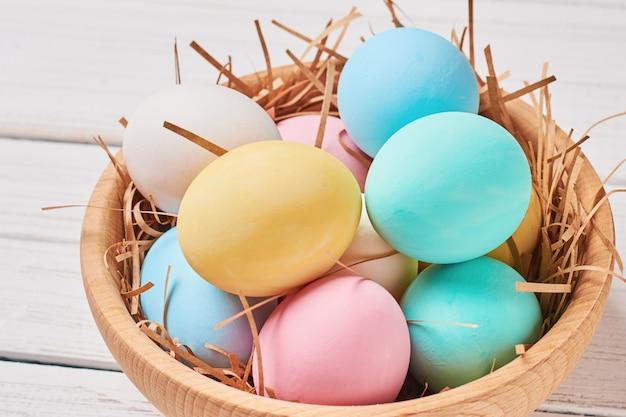 Ovos de páscoa colorgul em uma tigela de madeira close-up