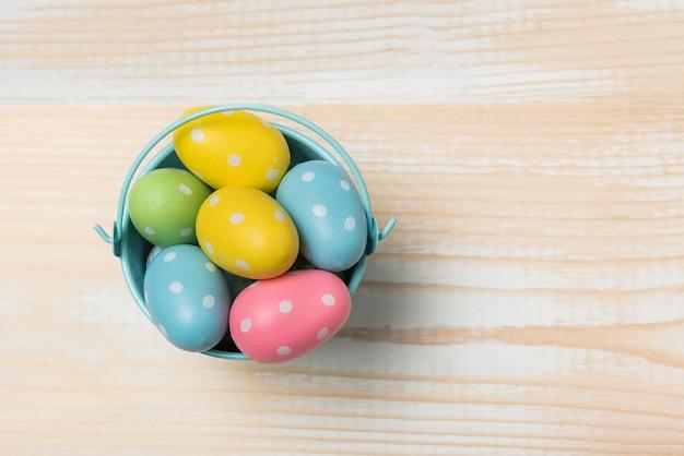 Ovos de páscoa coloridos brilhantes em um balde. madeira clara