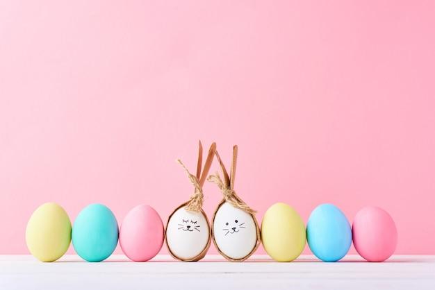 Ovos de páscoa coloridos com caras pintadas e orelhas de coelho em linha em um fundo rosa