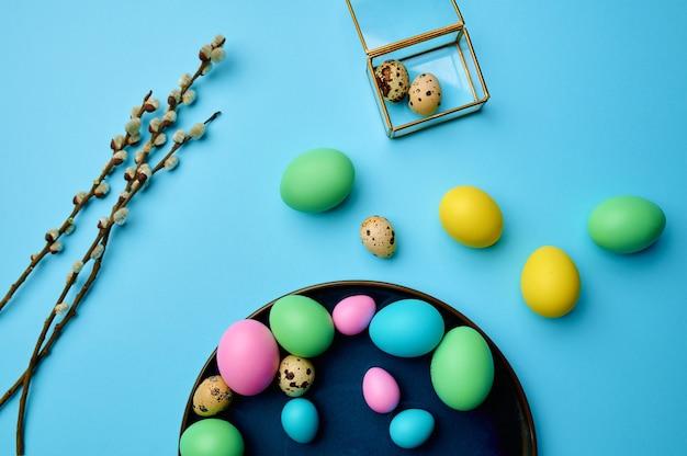 Ovos de páscoa coloridos com decoração na mesa azul, vista superior.
