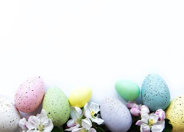 Ovos de páscoa coloridos com flores da flor da primavera isolados sobre a mesa branca. fronteira de férias de ovo colorido.