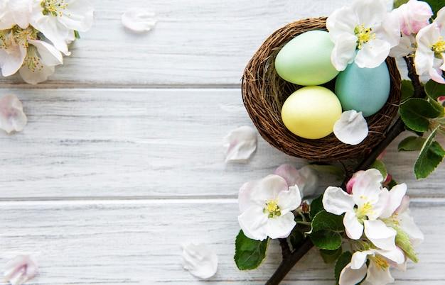Ovos de páscoa coloridos com flores da flor da primavera, mesa de madeira. fronteira de férias de ovo colorido.