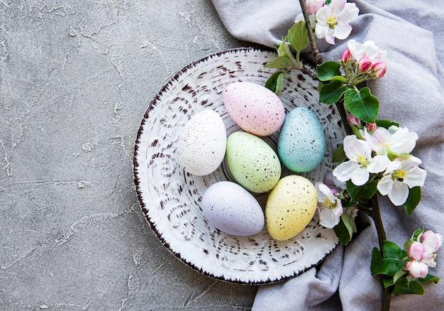 Ovos de páscoa coloridos com flores de flor de primavera, mesa de concreto cinza.