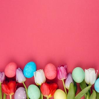 Ovos de páscoa coloridos com flores de tulipa na mesa vermelha