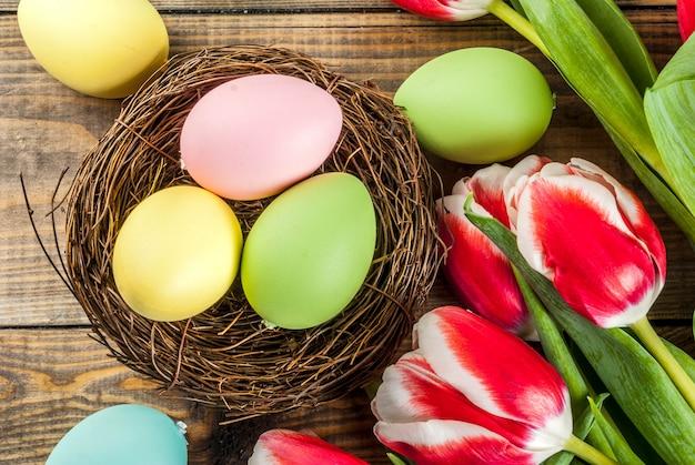Ovos de páscoa coloridos com flores tulipas em fundo de madeira,