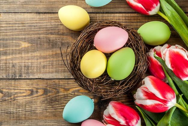 Ovos de páscoa coloridos com flores tulipas na vista superior de madeira, copyspace