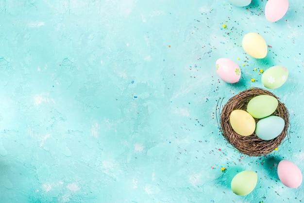 Ovos de páscoa coloridos com ninho de pássaro decorativo e açúcar polvilha sobre um fundo azul claro, copie o espaço