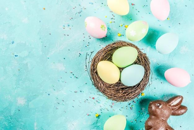 Ovos de páscoa coloridos com ninho de pássaro decorativo e polvilha de açúcar