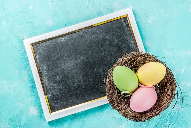 Ovos de páscoa coloridos com ninho decorativo em um azul claro,