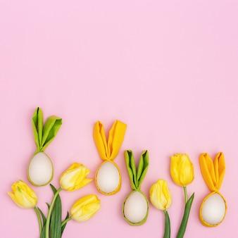 Ovos de páscoa coloridos com orelhas de pano como coelhinho da páscoa. a mola verde-clara e amarela floresce a tulipa no rosa com espaço da cópia. conceito de primavera de férias.