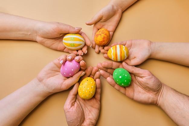 Ovos de páscoa coloridos de madeira nas mãos de uma família amigável depois de um egghunt