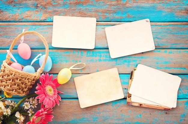 Ovos de páscoa coloridos e álbum de fotos de papel velho vazio na mesa de madeira