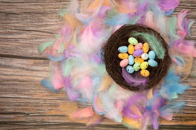 Ovos de páscoa coloridos e brilhantes em um ninho de pássaro com penas coloridas em tons pastel e mesa de madeira