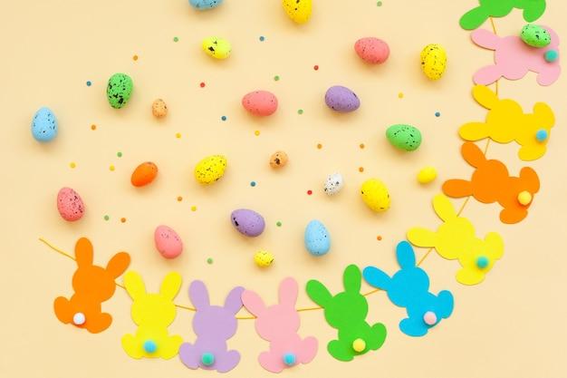 Ovos de páscoa coloridos e festão da páscoa coelhinho feito à mão em fundo bege. vista superior, configuração plana. conceito de feliz páscoa.