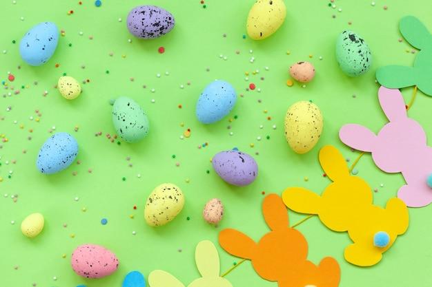 Ovos de páscoa coloridos e guirlanda de páscoa de coelho feito à mão sobre fundo verde. vista superior, configuração plana. conceito de feliz páscoa.