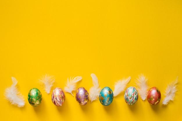 Ovos de páscoa coloridos e penas brancas sobre fundo amarelo. copie o espaço.