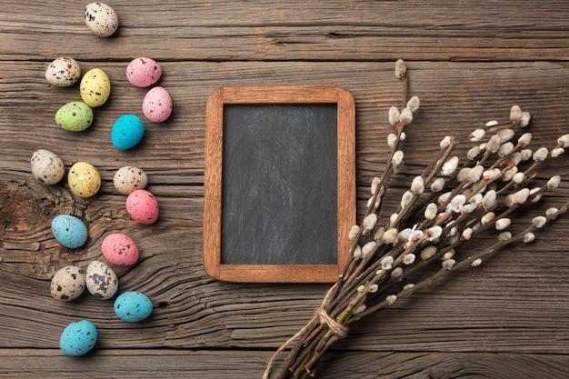 Ovos de páscoa coloridos e pincéis na mesa de madeira. vista superior com espaço de cópia.