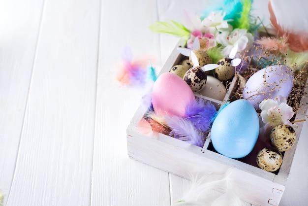 Ovos de páscoa coloridos em caixa de madeira em branco