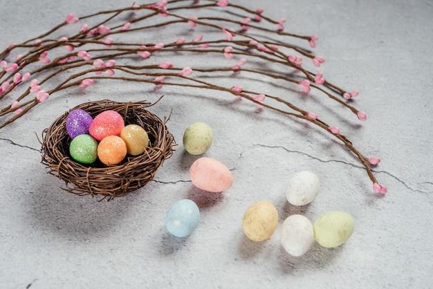 Ovos de páscoa coloridos em ninhos de pássaros com ramos decorativos de salgueiro