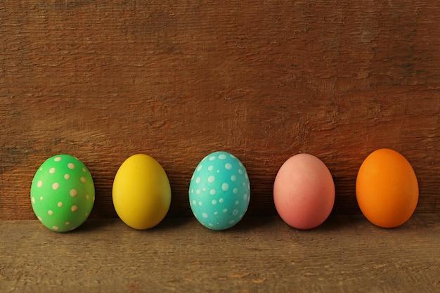 Ovos de páscoa coloridos em superfície de madeira