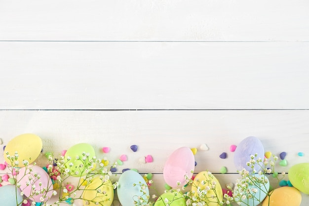 Ovos de páscoa coloridos em tons pastéis com flores sobre fundo branco de madeira