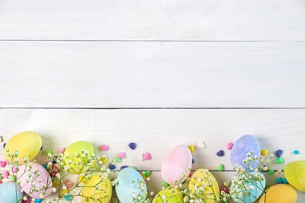 Ovos de páscoa coloridos em tons pastéis e pequenas flores na mesa de madeira branca, cópia espaço, vista superior