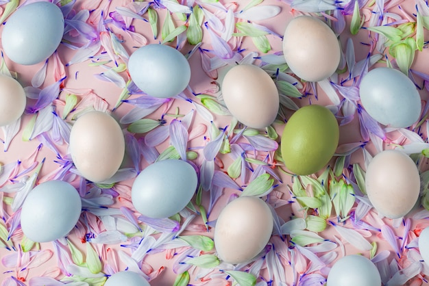 Ovos de páscoa coloridos em um fundo de pétalas de flores, composição de primavera. cores suaves de ouro, azul e branco, pétalas de rosa e azuis