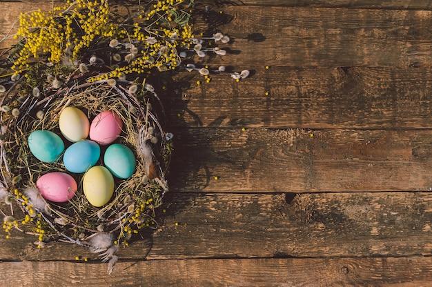 Ovos de páscoa coloridos em um lindo ninho. no contexto de uma velha placa de madeira.