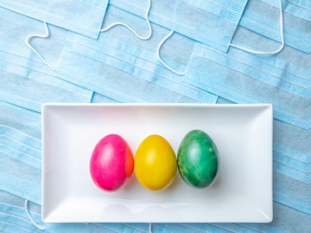 Ovos de páscoa coloridos em um prato branco sobre um fundo de máscaras médicas azuis