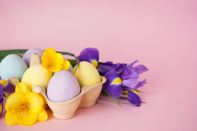 Ovos de páscoa coloridos em uma bandeja e flores em um fundo rosa. espaço para texto