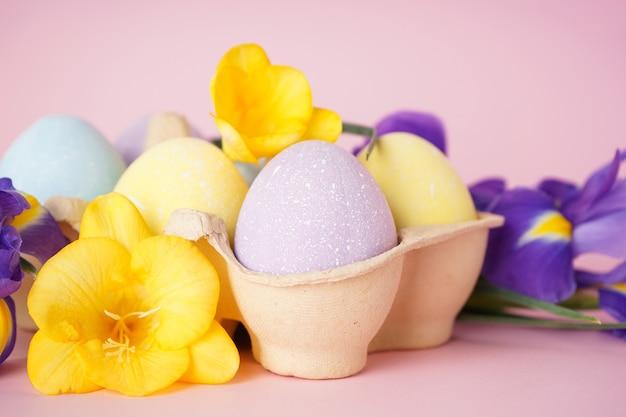 Ovos de páscoa coloridos em uma bandeja e flores em um fundo rosa. fechar-se. conceito de feliz páscoa.